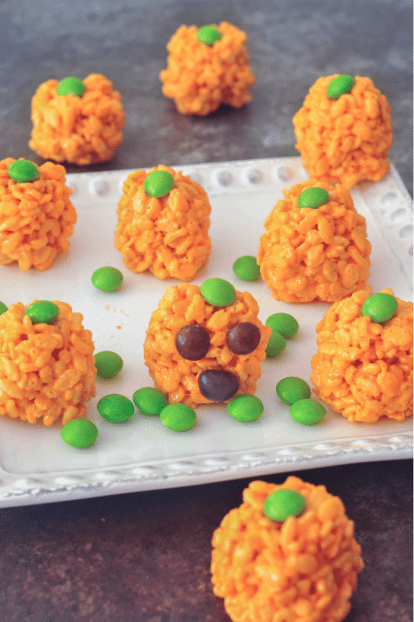 a large platter of vegan rice crispy treats colored orange and rolled into pumpkin shapes for Halloween. green candy on top for pumpkin stem. more green candy scattered on the platter, for pumpkin patch greenery.