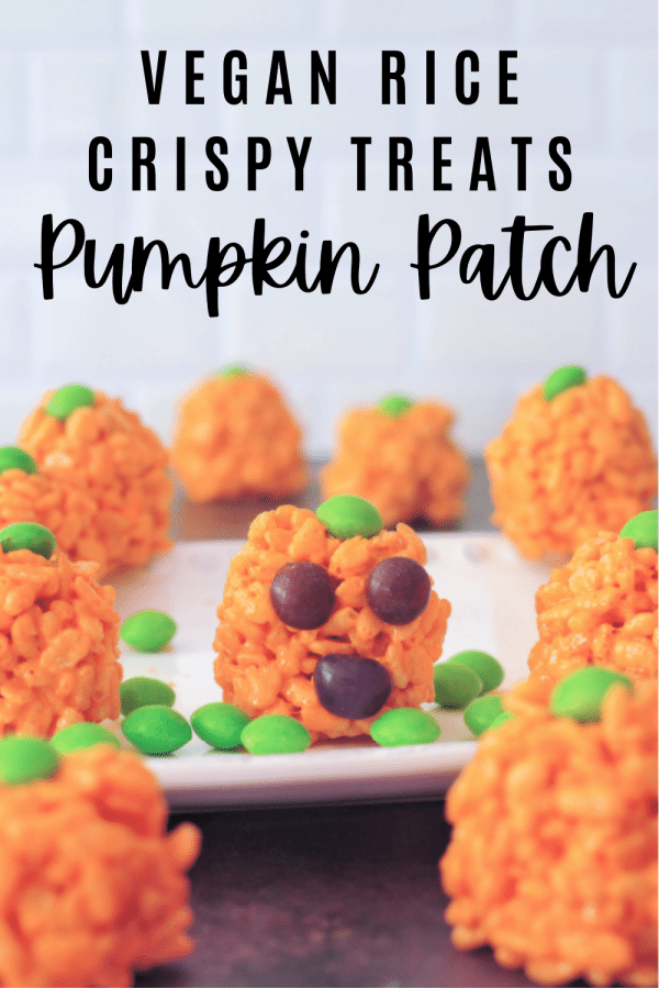 Vegan rice crispy treats colored orange and rolled into pumpkin shapes for Halloween. green candy on top for pumpkin stem.