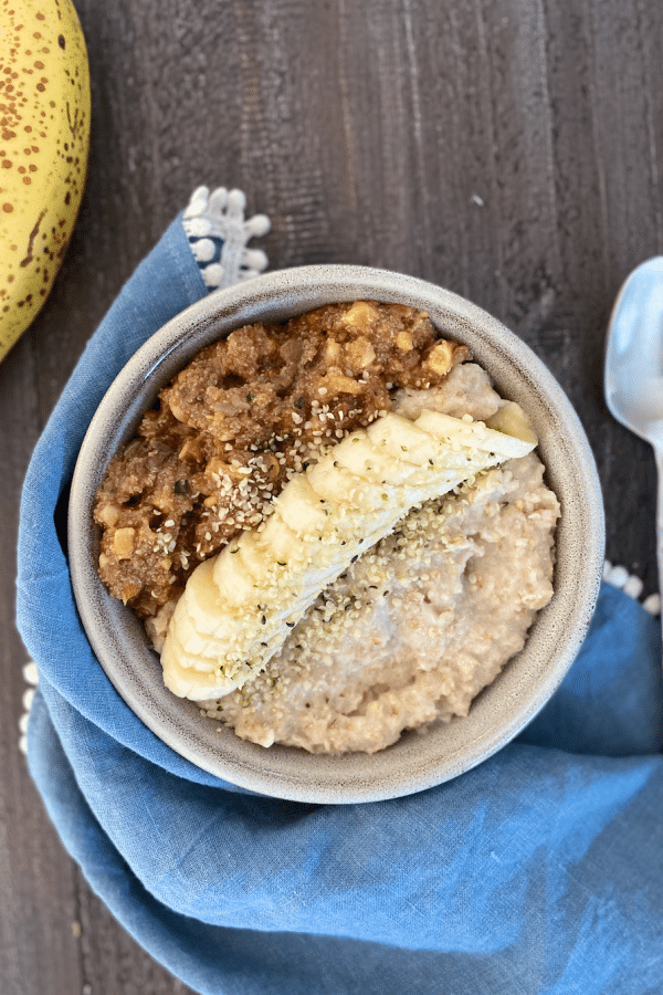 a bowl of amaranth and oatmeal, topped with a sliced banana and hemp seeds.
