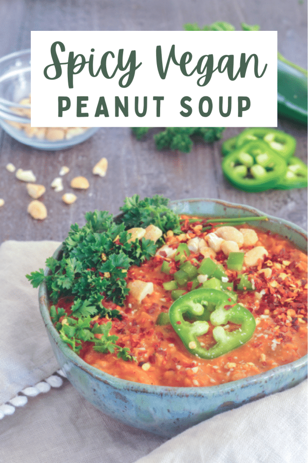 a rustic grey bowl of bright orange spicy vegan peanut soup, topped with parsley, sliced jalapeno, chopped peanuts