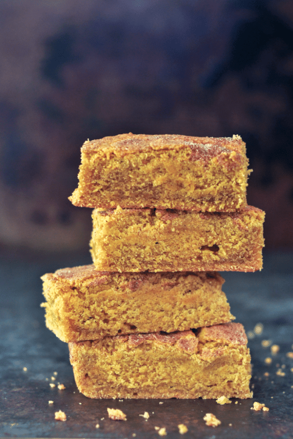 side view of a stack of four vegan pumpkin blondie squares against a dark background.