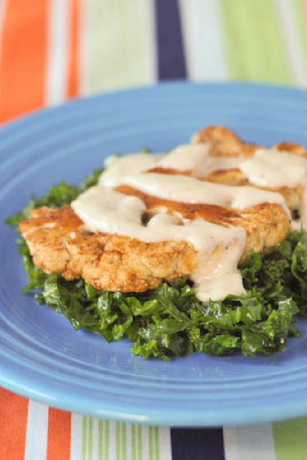a cauliflower steak without breading, served with a cheese sauce over chopped kale salad