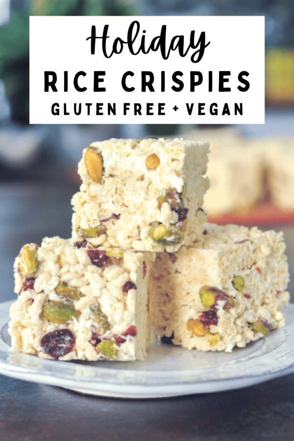a stack of vegan holiday rice crispies - marshmallow treat squares filled with deep red dried cranberries and bright green pistachios