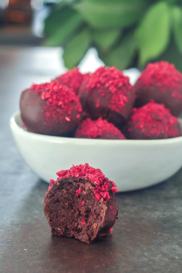 chocolate truffles with freeze dried raspberry dust in a white bowl, one out of the bowl and sliced in half to show the brownie filling.