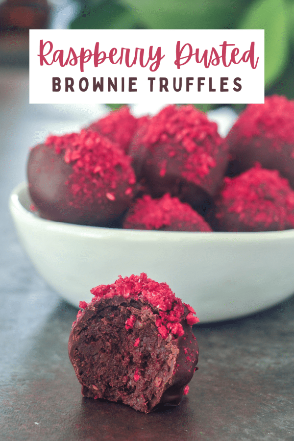 dark chocolate truffles with freeze dried raspberry dust in a white bowl, one out of the bowl and sliced in half to show the brownie filling.