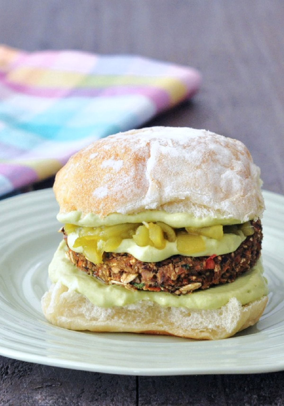 a veggie burger topped with avocado sauce and Hatch chiles