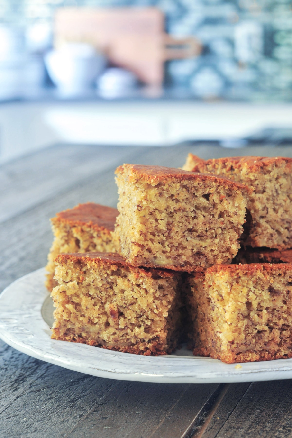 squares of banana snack cake stacked on a rustic dish, on a wooden table against a blurred kitchen background.