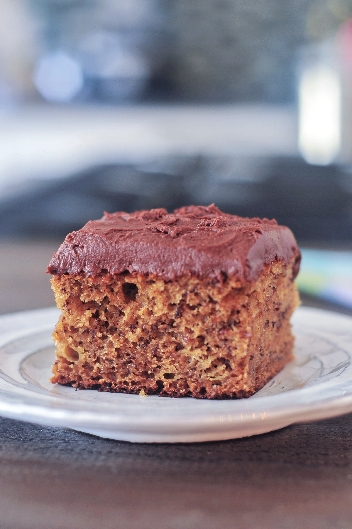 one square of banana snack cake with chocolate frosting on a small dessert plate against a blurred background.