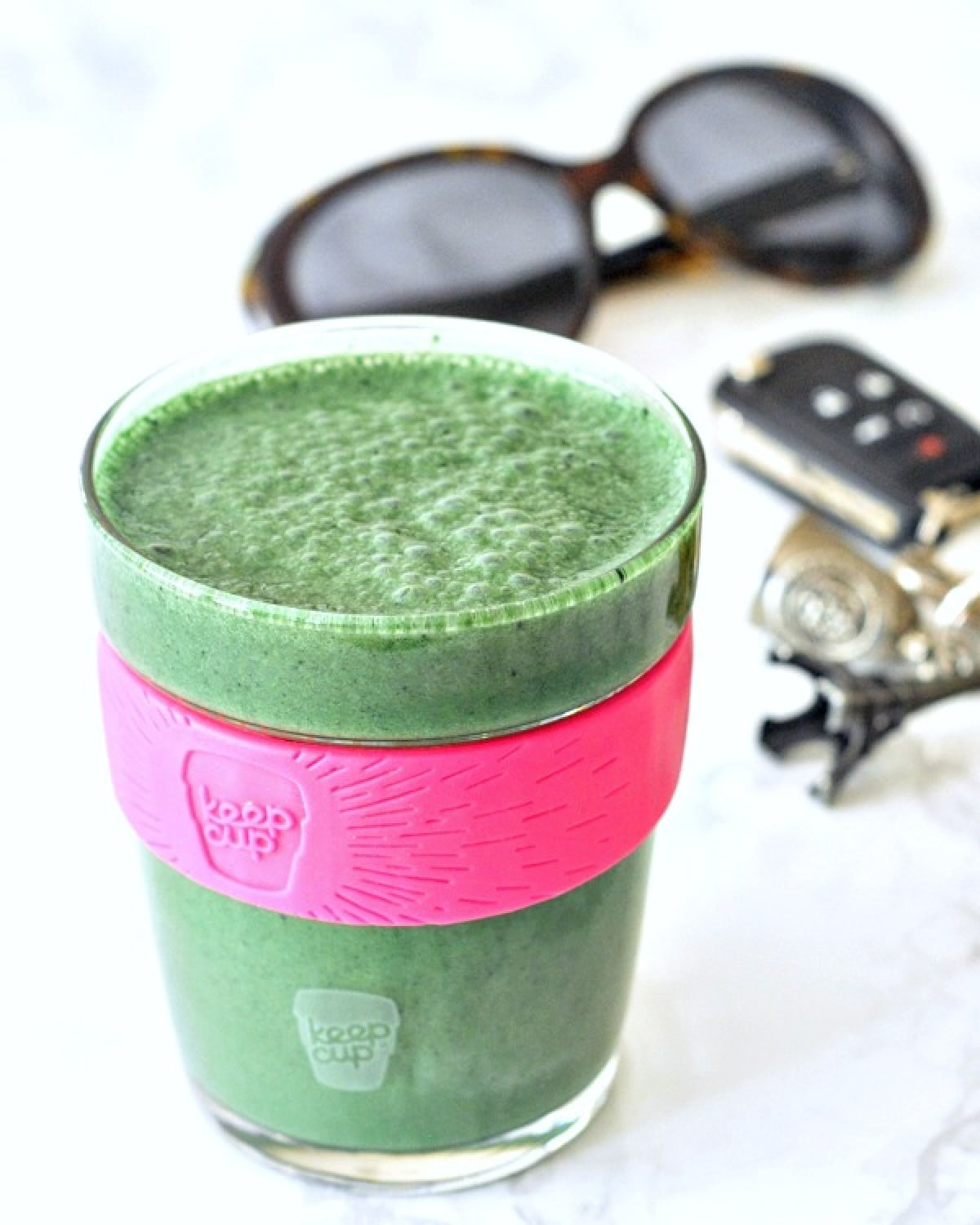 a green lemon spinach smoothie in a glass travel cup on a white marble countertop; car keys and sunglasses in background.