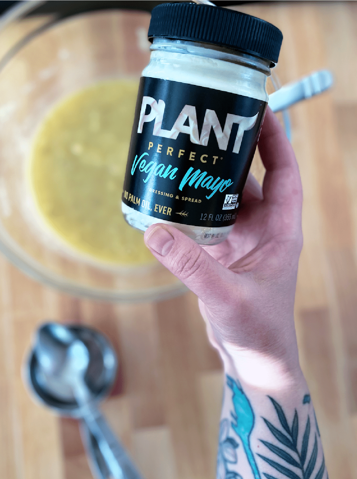 a tattooed hand holding a jar of vegan mayonnaise over a mixing bowl of snack cake ingredients.